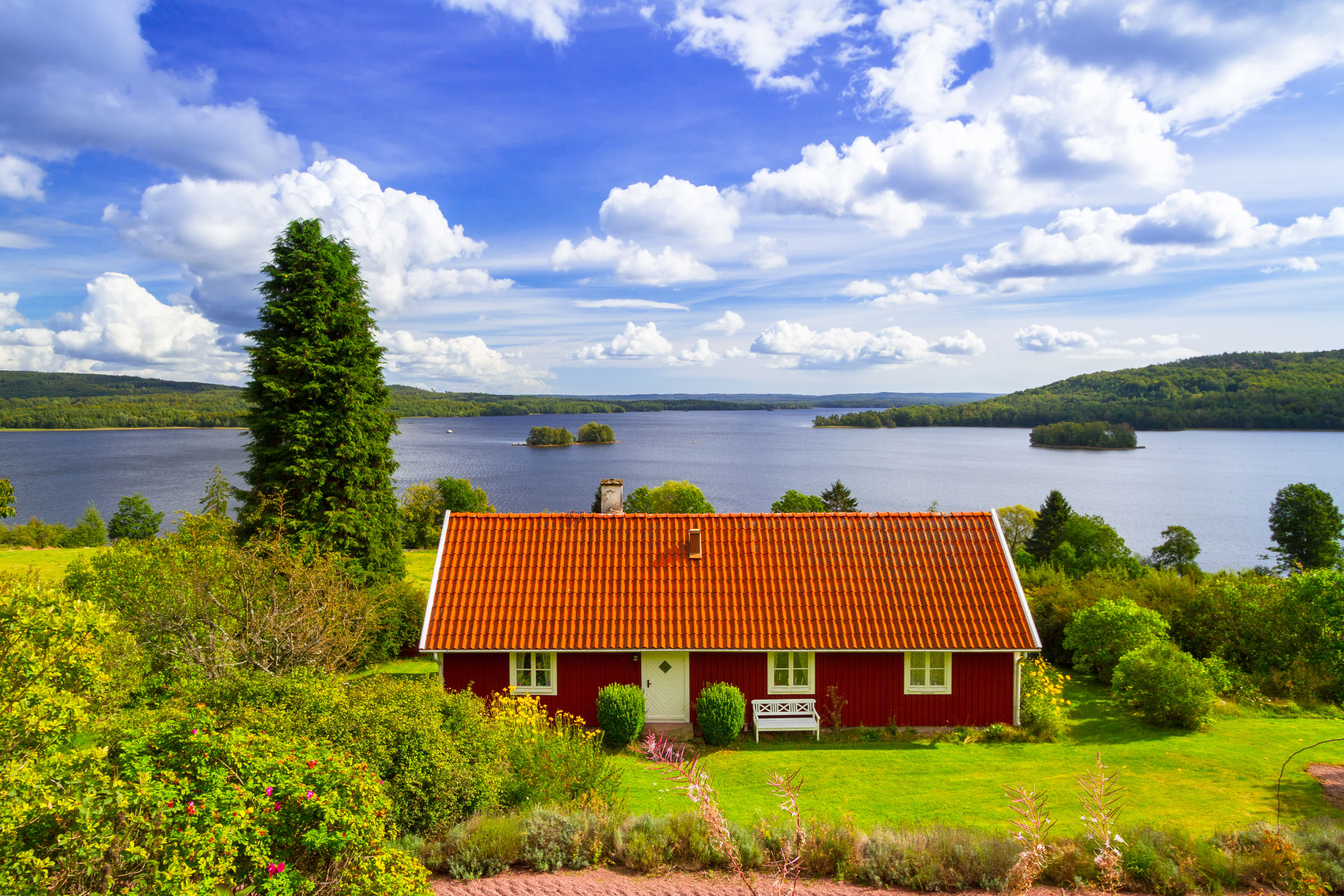 Traditional red cottage house at the lake in Sweden